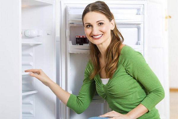 Девушка стоит около открытого холодильника