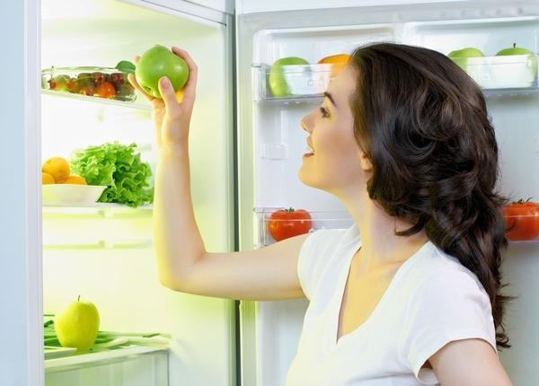 Девушка кладет яблоко в холодильник