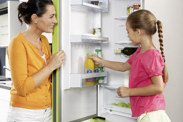 Женщина и ребенок у открытого холодильника