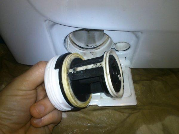 Вынутый сливной фильтр стиральной машины