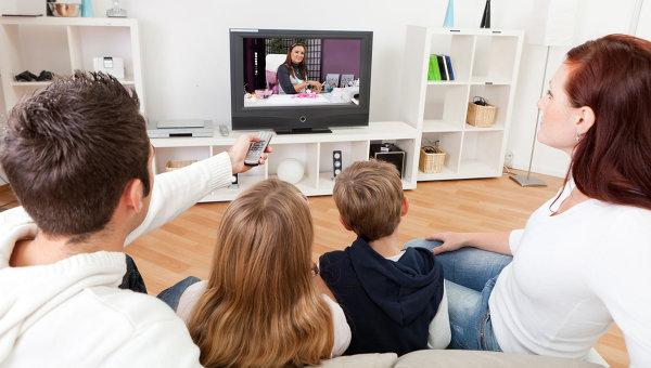 Семья в гостиной смотрит телевизор