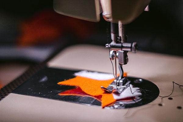 Игла с ниткой в швейной машинке