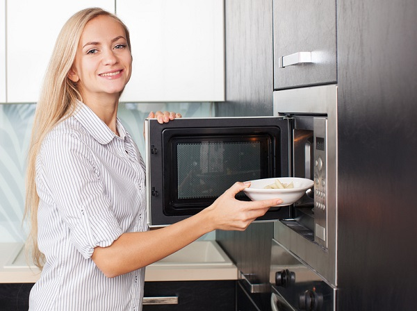 Женщина ставит тарелку в микроволновку