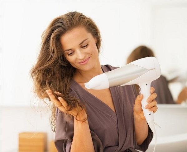 Молодая женщина сушит волосы