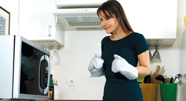 Девушка в кухонных перчатках возле микроволновки