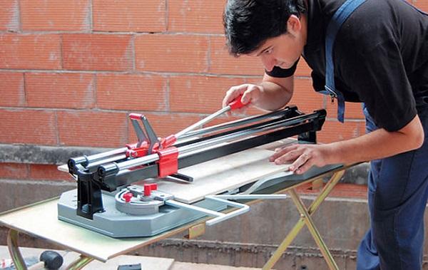 Мужчина режет плитку плиткорезом