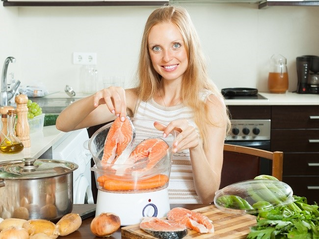 Молодая женщина готовит в пароварке