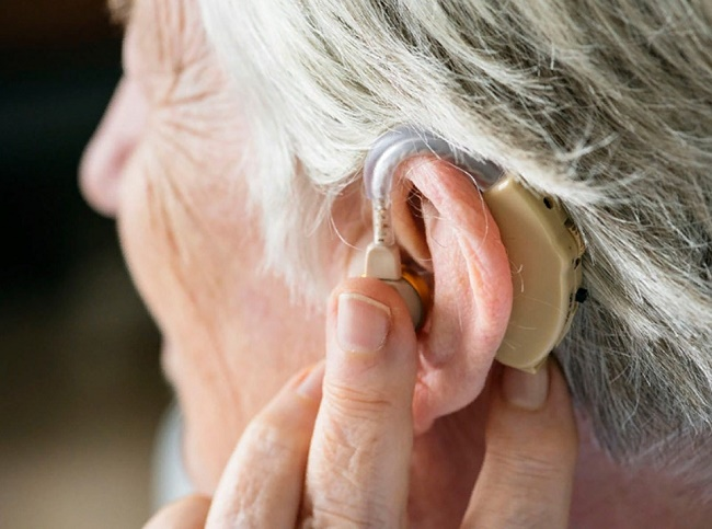 Слуховой аппарат на пожилой женщине