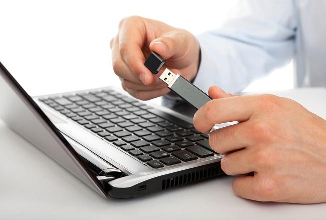 Флешка в руках и ноутбук