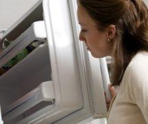 Девушка смотрит в морозильную камеру