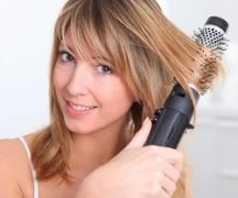Девушка сушит волосы феном-щеткой